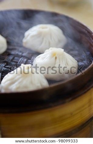 Chinese cuisine, steamed buns with stuffing in the bamboo steamer. - stock photo