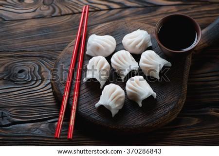 Chinese dim sum dumplings in a rustic wooden setting, closeup - stock photo