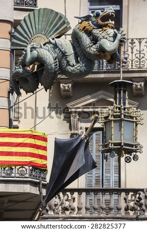 Chinese Dragon and umbrella, modernism architecture (Casa Bruno Cuadros),with the Catalan flag background, in Barcelona, Spain. Is an old store of umbrellas, canes and fans of mid-nineteenth century. - stock photo