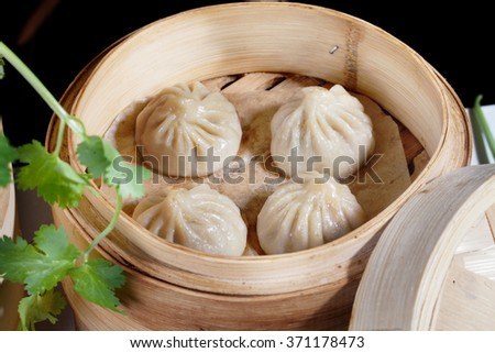 Chinese dumplings in a wooden steamer in the still life on a table the national atmosphere of great food - stock photo