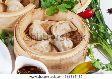 Chinese dumplings wooden steamer still life on a table the national atmosphere - stock photo
