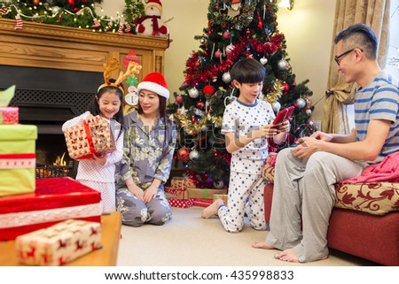 Chinese family opening presents together on Christmas morning. They are all sitting in the front room in their pyjamas, in front of the tree. - stock photo