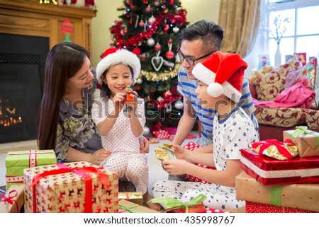 Chinese family opening their presents together on Christmas morning. they are all sitting on the floor in their living room, in front of the tree.  - stock photo