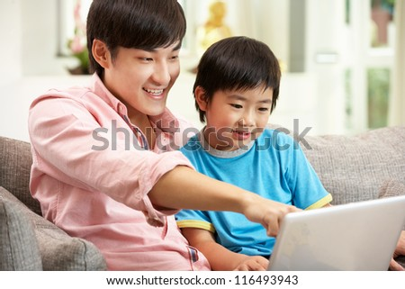 Chinese Father And Son Using Laptop Whilst Relaxing On Sofa At Home - stock photo
