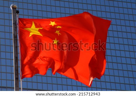 Chinese flag with a modern office building backdrop.  - stock photo