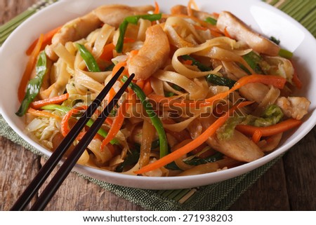 Chinese Food: Chow mein with chicken and vegetables on a table close-up. horizontal  - stock photo
