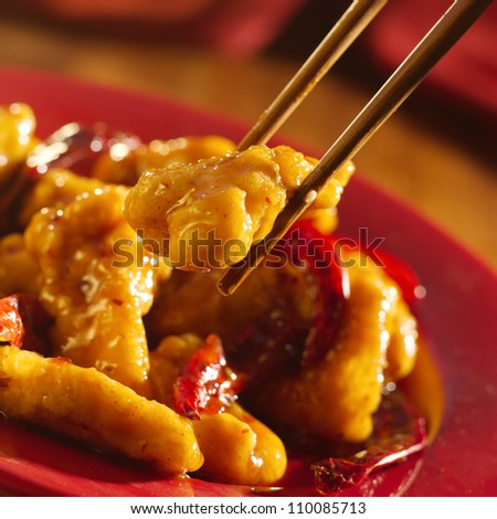 Chinese food - Eating General Tso's chicken with chopsticks. - stock photo