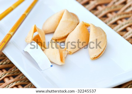 Chinese Fortune Cookie with blank paper on white dish with chop sticks. Shallow DOF - stock photo