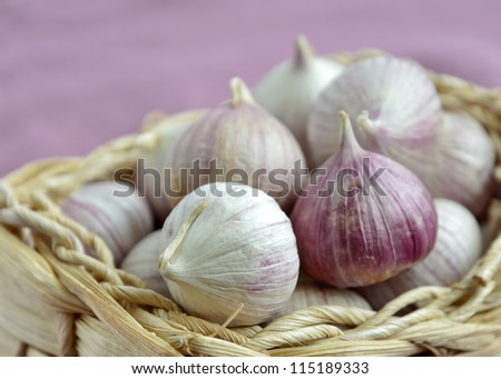 Chinese garlic in a wicker basket, shallow depth of field. - stock photo