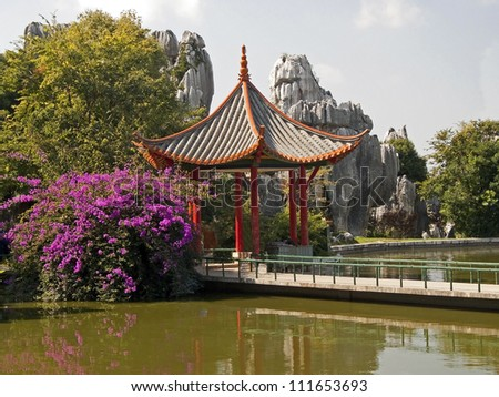 Chinese gazebo located in a beautiful garden on the banks of the pond - stock photo