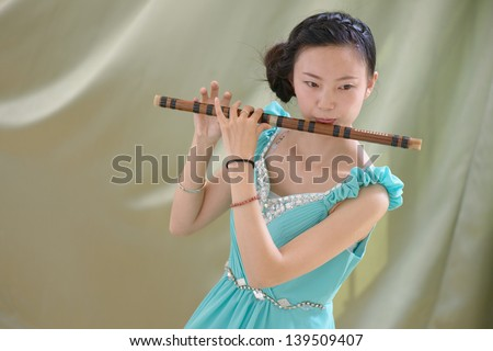 Chinese girl blowing bamboo flute - stock photo