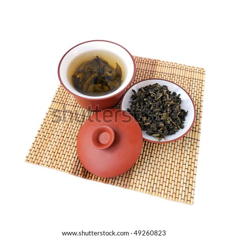 Chinese green tea in the ceramic bowl with cover and tea leaves - stock photo