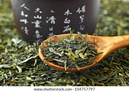 Chinese green tea on wooden spoon with a cup - stock photo