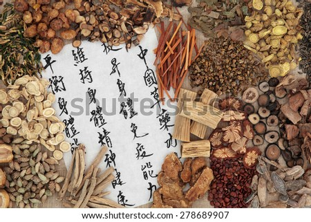 Chinese herb selection with calligraphy script. Translation describes chinese herbal medicine as increasing the bodys ability to maintain body and spirit health and balance energy. - stock photo
