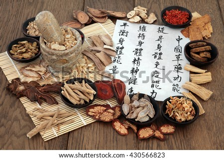 Chinese herbal medicine with herb ingredients and calligraphy. Translation reads as Chinese herbal medicine as increasing the body's ability to maintain body and spirit health and balance energy. - stock photo