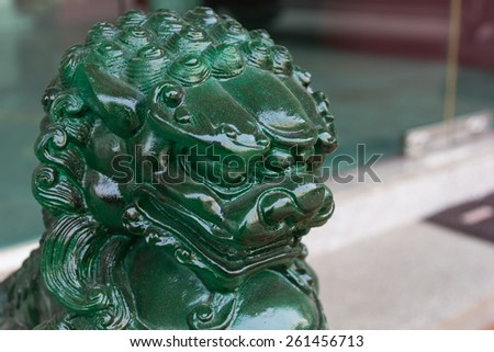 Chinese Jade Lion Statue on blur background. - stock photo