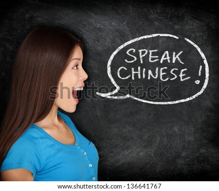 Chinese language learning concept. Woman speech bubble on blackboard saying SPEAK CHINESE. Fun happy mixed race student or teacher. - stock photo
