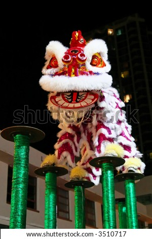 Chinese lion dance jumping on high poles - stock photo