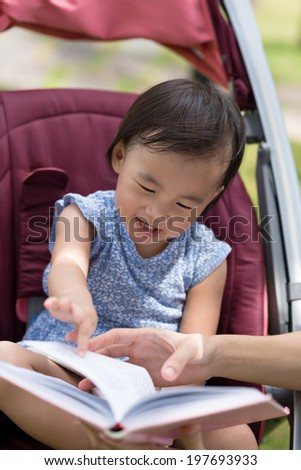 Chinese little girl trying to read a book while sitting in the baby carriage - stock photo