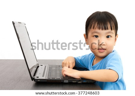 Chinese little girl using laptop in plain isolated white background. - stock photo
