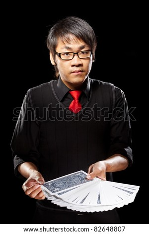 Chinese male magician holding cards against dark background - stock photo