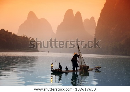 Chinese man fishing with cormorants birds, Yangshuo, Guangxi region, traditional fishing use trained cormorants to fish - stock photo