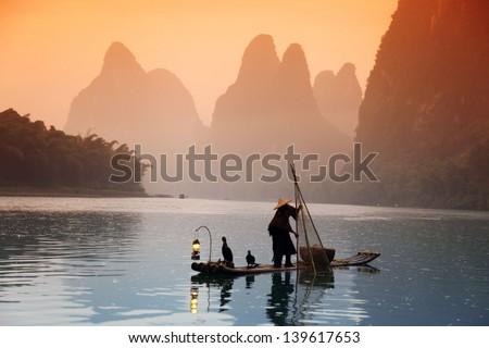 Chinese man fishing with cormorants birds, Yangshuo, Guangxi region, traditional fishing use trained cormorants to fish - stock photo