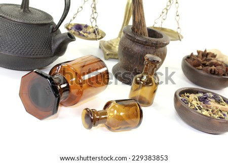 Chinese medicine with herbs and apothecary bottle on light background - stock photo