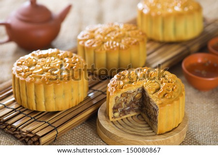 Chinese mid autumn festival foods. Traditional mooncakes on table setting.  The Chinese words on the mooncakes means assorted fruits nuts, not a logo or trademark. - stock photo