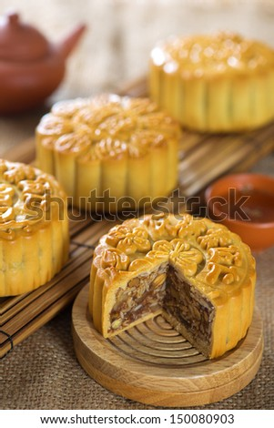 Chinese mid autumn festival foods. Traditional mooncakes on table setting with tea set.  The Chinese words on the mooncakes means assorted fruits nuts, not a logo or trademark. - stock photo