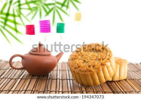 Chinese mid autumn festival foods with blank copy space. Traditional mooncakes on table setting with teacup. The Chinese words on the mooncakes means assorted fruits nuts, not a logo or trademark. - stock photo