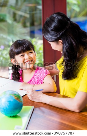 Chinese mother doing school homework with child or homeschooling daughter - stock photo