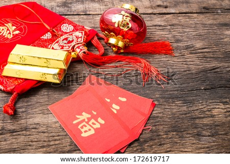 Chinese new year decoration, Chinese tassel, Chinese lantern, Chinese red tag, Chinese red bag and golden bullion on wooden table - stock photo