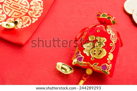 """Chinese new year decoration: red felt fabric packet or ang pow with word """"prosperous"""" and golden ingots on red fabric. - stock photo"""
