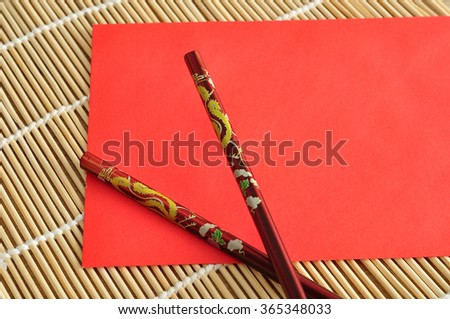 Chinese New Year design. A red envelope for money in the Chinese New Year isolated on a bamboo background with chopsticks - stock photo
