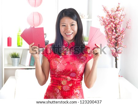 chinese new year girl with ang pow red packet, with decorations on background - stock photo