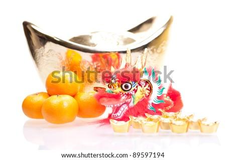 Chinese new year with dragon decoration, large gold ingot and mandarin oranges - stock photo