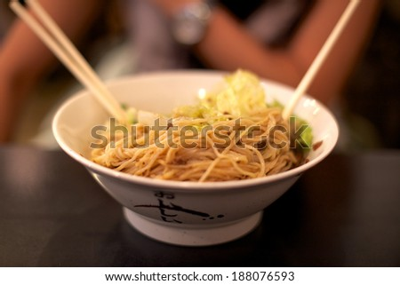 Chinese noodle dish set out on a table at a restaurant in Chinatown Manhattan, New York, NY, USA. - stock photo