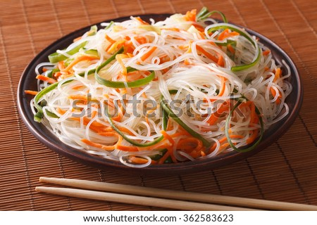 Chinese noodles with cucumber and carrot on a plate close-up. horizontal - stock photo