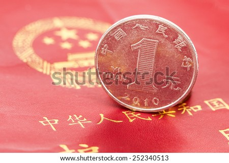 Chinese one yuan coin against the background of the Chinese passport - stock photo