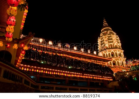 chinese pagoda temple lighted up with lanterns hanging in front - stock photo