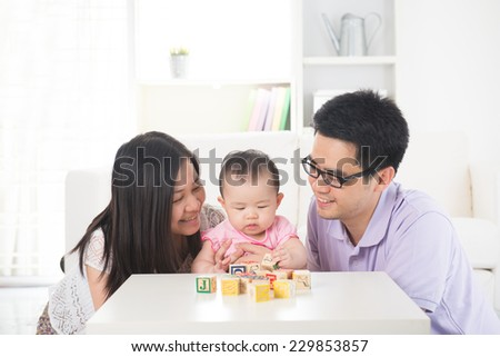 chinese parent playing with baby  - stock photo