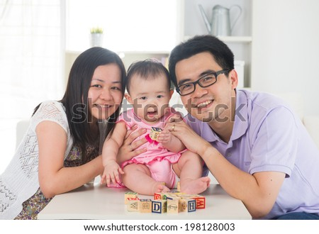 chinese parent playing with baby girl in livingroom - stock photo