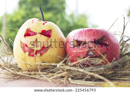 Chinese pear and apple for halloween on hay green background - stock photo
