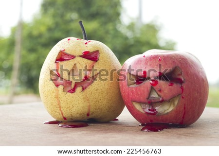 Chinese pear and apple for halloween on wood - stock photo