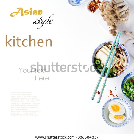 Chinese porcelain bowl of asian ramen soup with feta cheese, noodles, spring onion and mushrooms, served with turquoise chopsticks and sliced egg over white background. Top view. With sample text - stock photo