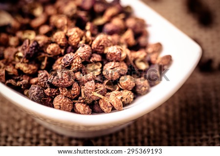 Chinese prickly ash on china dish with flax background film effect - stock photo