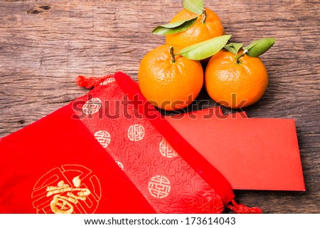 Chinese red pocket in Chinese red bag and mandarin orange on wooden table - stock photo