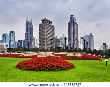 Chinese Shanghai city center around People's square park and surrounding skyscrapers around green grass with flowers - stock photo