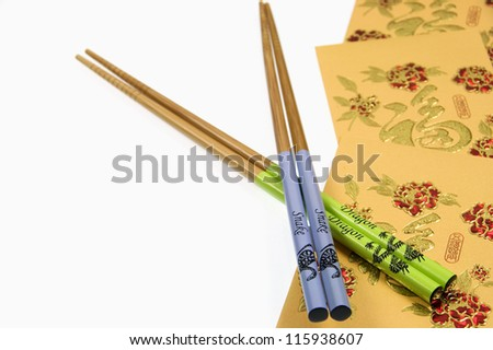 Chinese Snake and Dragon Chopsticks With Gold Money Wallets On White Background. Chinese New Year - stock photo